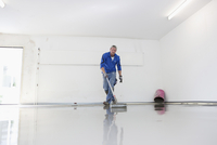 Tradesman Working on new Floor Cover in Garage, Mulheim, North Rhine-Westphalia, Germany