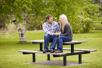 Young Couple Sitting on Picnic Table, Scanlon Creek Conservation Area, Bradford, Ontario, Canada
