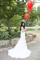 Portrait of bride outdoors, wearing wedding gown and holding red balloons, Ontario, Canada