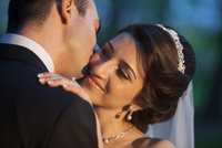 Close-up of groom kissing bride on cheek, outdoors, Ontario, Canada
