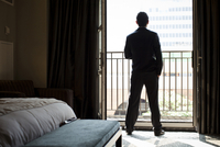Backview of Groom standing in bedroom, looking out at city from balcony, Toronto, Ontario, Canada