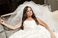 Portrait of bride lying on sofa, wearing wedding gown and veil, Ontario, Canada