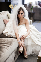 Portrait of bride sitting on sofa wearing wedding gown and veil, Ontario, Canada