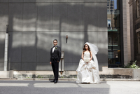 Bride and groom standing on city street, looking at camera, Toronto, Ontario, Canada