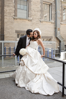 Groom kissing bride outdoors next to buildings, Toronto, Ontario, Canada