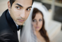 Close-up portrait of groom, with bride in the background, Ontario, Canada