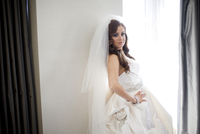 Portrait of bride standing next to window, smiling and looking at camera, Ontario, Canada