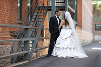 Bride and groom standing outdoors next to buildings, Toronto, Ontario, Canada