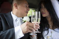 Close-up of Bride and Groom in car, looking at each other and toasting with champagne glasses on wedding day, Ontario, Canada