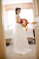 Portrait of bride wearing wedding gown and veil, standing in bedroom, looking at camera, Ontario, Canada