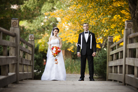 Portrait of bride and groom standing on bridge in public garden, in Autumn, looking at camera, Ontario, Canada 20025317212| 写真素材・ストックフォト・画像・イラスト素材|アマナイメージズ
