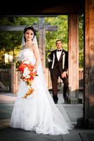 Portrait of bride standing outdoors in public garden, with groom standing in background, Ontario, Canada 20025317215| 写真素材・ストックフォト・画像・イラスト素材|アマナイメージズ