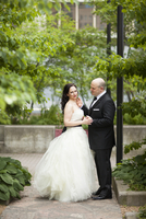 Portrait of bride and groom standing outdoors in garden, Ontario, Canada
