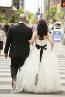 Backview of bride and groom walking across intersection of city street, Toronto, Ontario, Canada