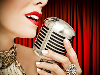 Close-up of a female's lips close to a classic microphone against a red curtain.