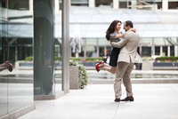 Excited couple embracing on ciity street sidewalk, Toronto, Ontario, Canada