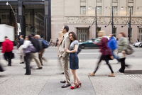 Couple standing on sidewalk on busy, city street, Toronto, Ontario, Canada
