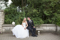Bride and Groom sitting on stone bench outdoors, holding hands and looking at each other on Wedding Day, Canada