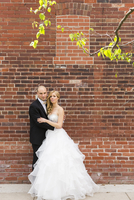 Portrait of bride and groom standing outdoors in front of brick wall, looking at camera and smiling, Canada