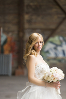 Portrait of blond, bride standing outdoors looking at camera and smiling, holding bridal bouquet on Wedding Day, Canada
