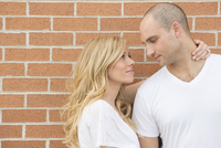 Close-up portrait of young couple standing in front of brick wall outdoors, smiling and looking at each other, Canada