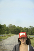 Young Woman in Cap Standing on Country Road