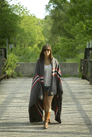 Young woman wrapped in blanket walking on bridge