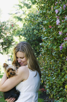 Portrait of woman holding yorkshire terrier outdoors, USA