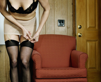 Woman fastening garters, getting dressed in home, USA