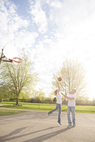 Couple playing basketball in neighbourhood park, Toronto, Ontario, Canada