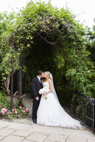 Bride and Groom standing outdoors under arbour, kissing on Wedding Day, Canada