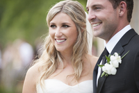 Close-up portrait of Bride and Groom smiling outdoors on Wedding Day, Canada