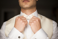 Close-up of Groom adjusting bow tie and getting ready on Wedding Day, Canada
