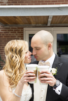 Close-up of Bride and Groom toasting eatch other with cups of coffee outdoors on Wedding Day, Canada