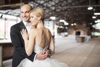 Close-up portrait of bride and groom standing in banquethall, smiling and embracing, Canada