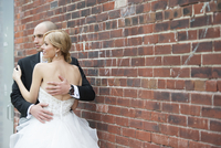 Portrait of Bride and Groom standing in front of brick wall, embracing outdoors on Wedding Day, Canada