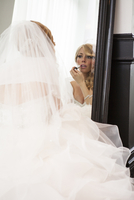 Portrait of Bride looking in mirror and applying make-up, getting ready on Wedding Day, Canada
