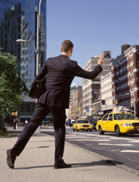 Businessman Hailing a Cab with Waffle in his Hand, New York City, New York, USA