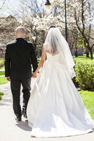 Backview of bride in wedding gown with bridegroom, holding hands and walking down pathway in park in Spring on Wedding Day, Cana