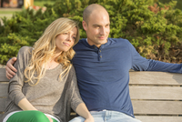 Portrait of young couple sitting on park bench together, outdoors, Canada