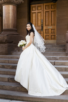 Portrait of Bride in wedding gown holding bridal bouquet, standing on stairs in front of building, smiling and looking at camera