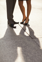 Close-up of young couples legs and feet with shadows, wearing dress shoes and standing on sidewalk, Canada