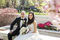 Portrait of Bride and groom sitting on stone bench in park in Spring, smiling and looking at camera, Canada