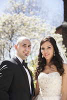 Close-up portrait of bride and groom standing outdoors on Wedding Day in Spring, smiling and looking at camera, Canada