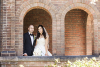 Portrait of bride and groom standing under brick archways on Wedding Day, smiling and looking at camera, Canada