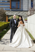 Portrait of bride in wedding gown with bridegroom in tuxedo, standing outdoors on Wedding Day, smiling and looking at camera, Ca
