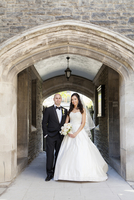Portrait of Bride and Groom standing under archway outdoors, smiling and looking at camera, Canada