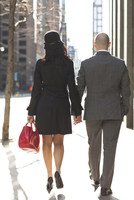 Backview of young couple in business wear, walking down city street, Toronto, Ontario, Canada