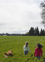 Backview of two girls walking in a field with their dog, Oregon, USA
