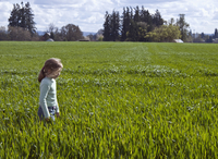 Young girl walking in field, Oregon, USA